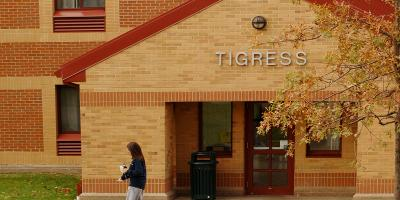 A female student walks past Tigress Residence Hall on the Penn State Behrend campus.