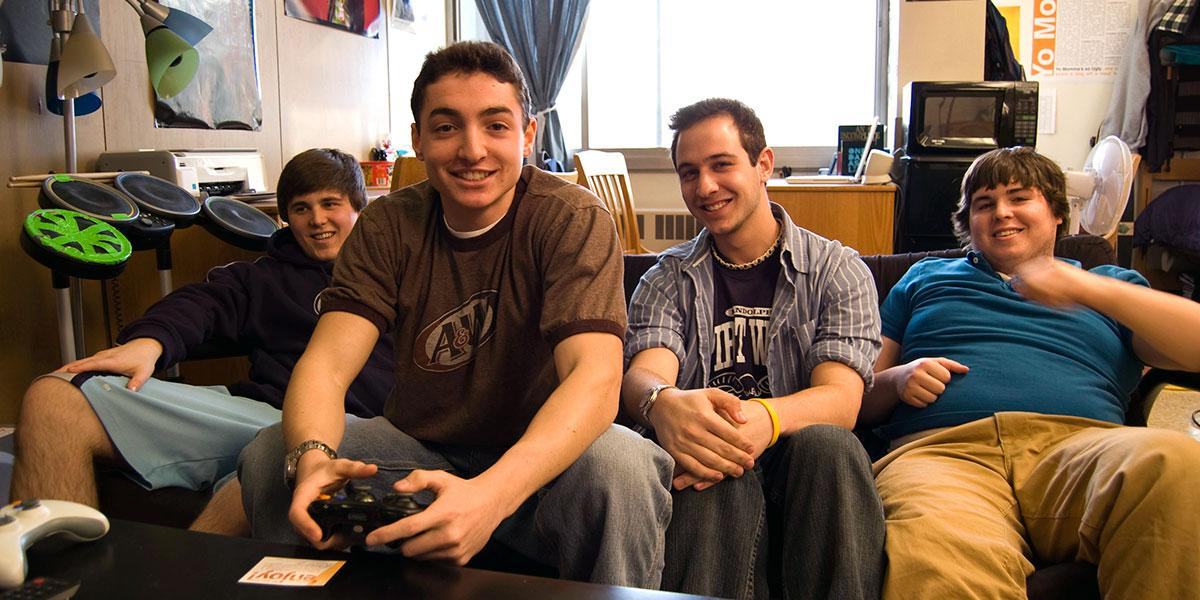 Four male students sitting on their couch in supplemental housing