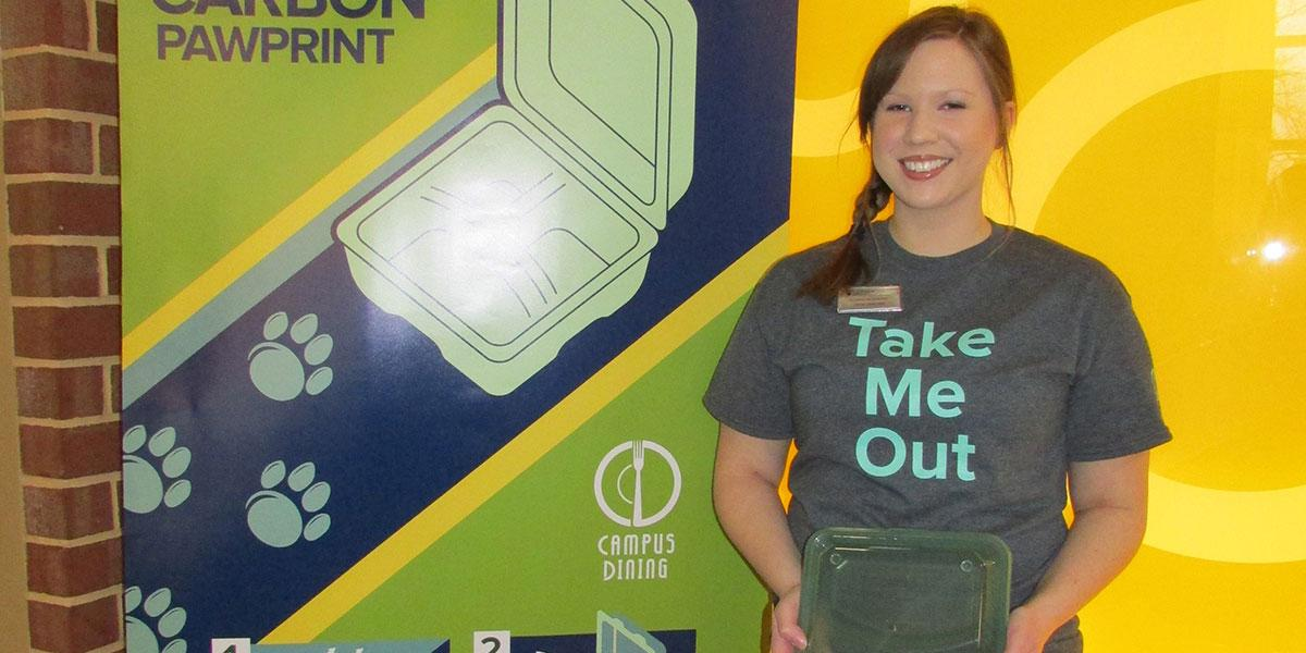 A student stands in front of a green to go poster and holds a green to go box.