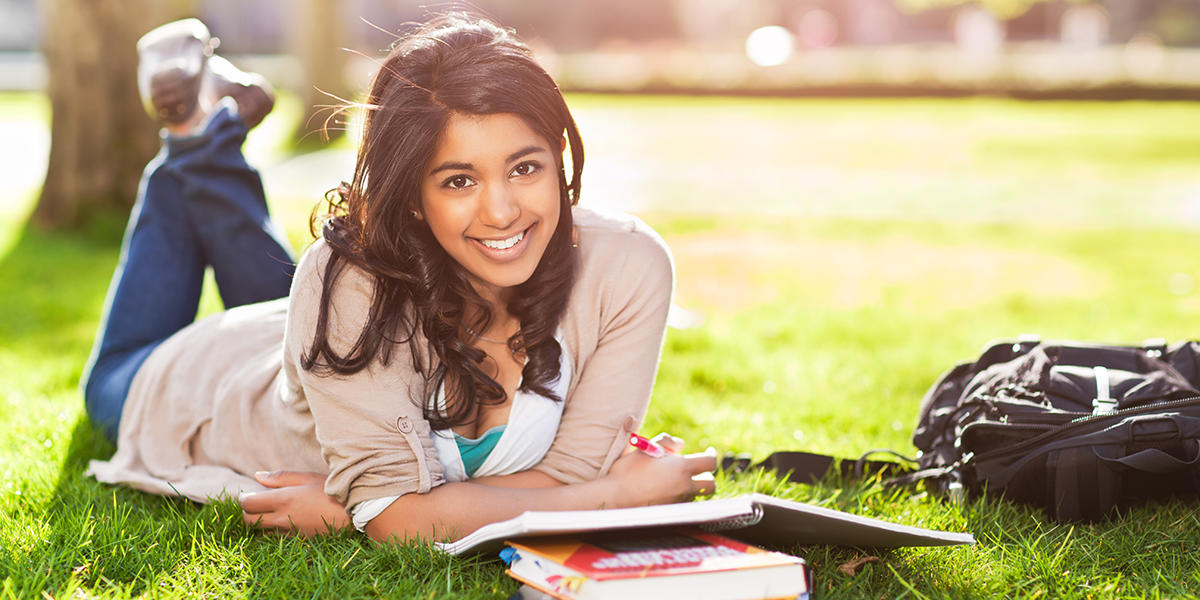 girl laying on sun-dappled grass next to open books and backpack